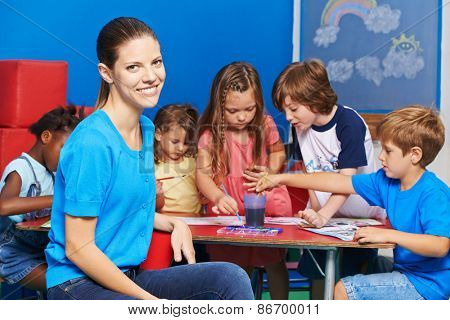 Woman as nursery teacher in kindergarten with group of children painting at table
