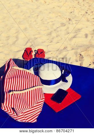hat, bag, touch pad, mobile phone and flip flops on tropical beach