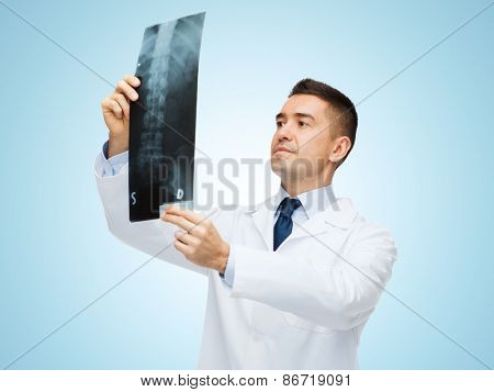 healthcare, roentgen, people and medicine concept - male doctor in white coat looking at x-ray over blue background