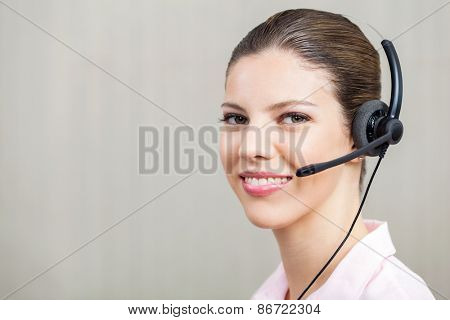 Portrait of smiling female employee wearing headset at call center