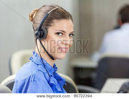 Portrait of beautiful customer service executive wearing headset in call center