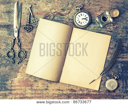Open Book And Antique Writing Tools On Wooden Table. Feather Pen, Inkwell, Keys