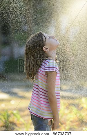 Happy little girl outdoor in a sunny day enjoying the light rain.