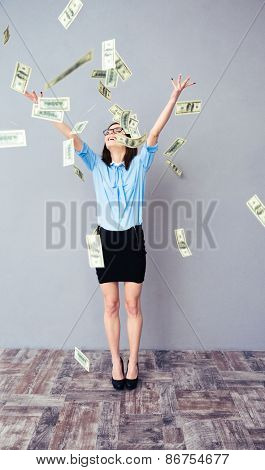 Business woman standing in the rain of the dollar bills looking very happy. Wearing in blue shirt, black dress and glasses.