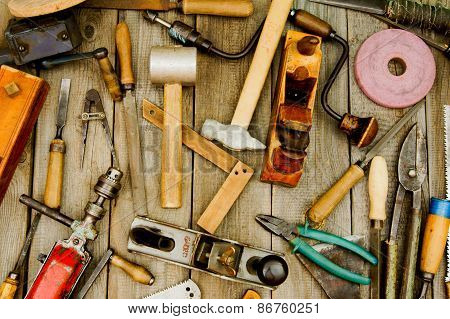 Vintage working tools on wooden background.