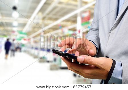 Business Man Using Mobile Phone While Shopping In Supermarket.