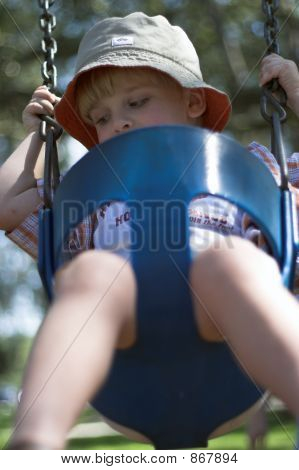 Young Boy On Swing At Playground