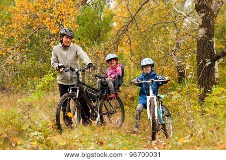 Happy family on bikes in autumn park, having fun, sport and cycling with kids