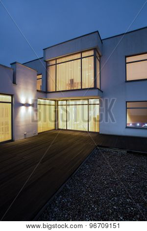 Illuminated windows in detached house - picture done at night poster