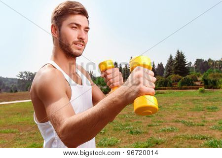 Pleasant guy holding weights