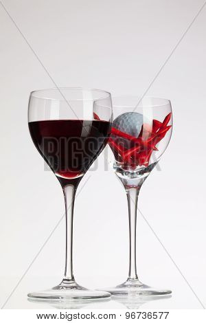 Wine Glasses With Red Wine And Golf Ball