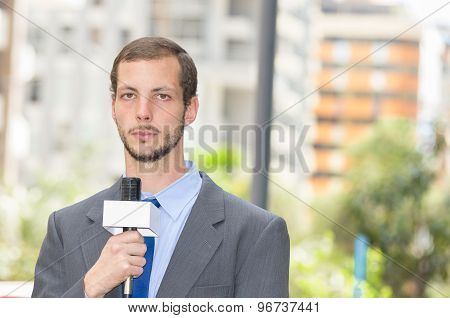 Attractive professional male news reporter wearing grey suit holding microphone, talking to camera f