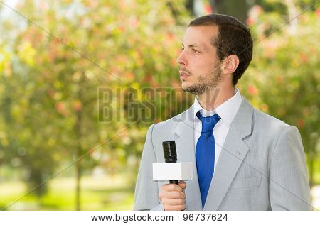 Successful handsome male news reporter wearing light grey suit working outdoors park environment hol