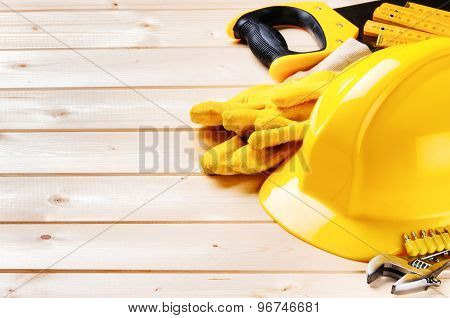 Hard Hat And Various Tools On Wooden Background