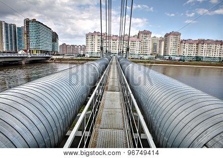 Heating Duct Crosses River On Cable-stayed Bridge In Residential Area.