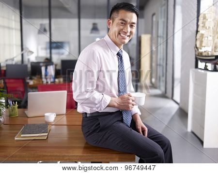 Portrait Of A Happy Asian Business Executive In Office