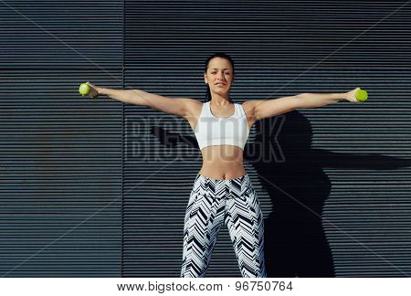 Smiling beautiful female exercising or working on her arms at outdoors while looking to you