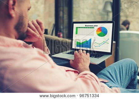 Young entrepreneur analyzing performance on his notebook male freelancer work in interior