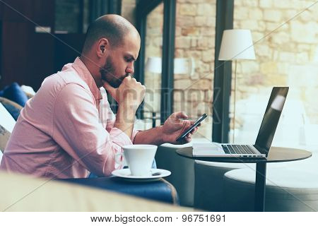 Young business man use laptop sitting at sofa of modern coffee shop or hotel hall