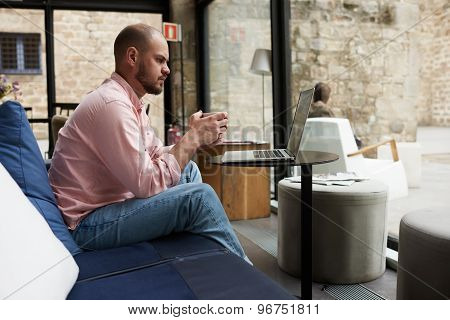 Pensive young business man sitting front open laptop computer holding cup of coffee or tea