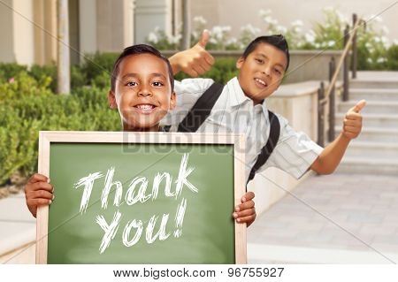 Happy Hispanic Boys Giving Thumbs Up Holding Thank You Chalk Board Outside on School Campus.