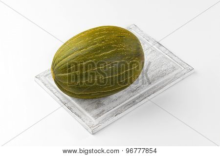 fresh piel de sapo melon on wooden cutting board