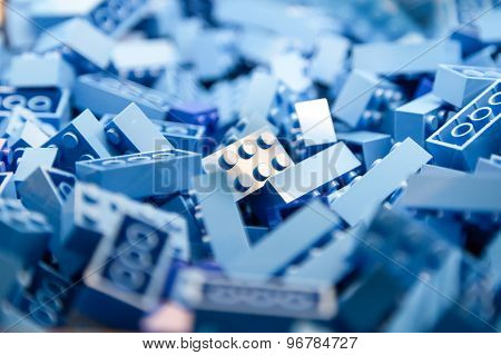 Pile of blue color building blocks with selective focus and highlight on one particular block