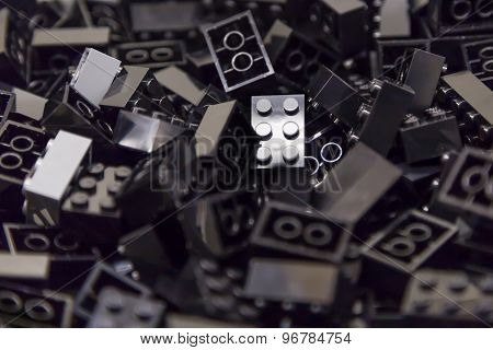 Pile of black color building blocks with selective focus and highlight on one particular block