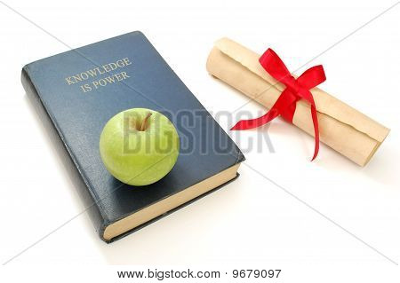 Book entitled knowledge is power next to a education diploma poster
