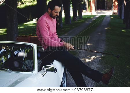 Wealthy man leaning on his convertible luxury car preparing for golf game at recreation time