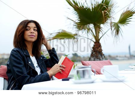 Carefree young woman enjoying a good day with book while sitting at sidewalk cafe near the beach