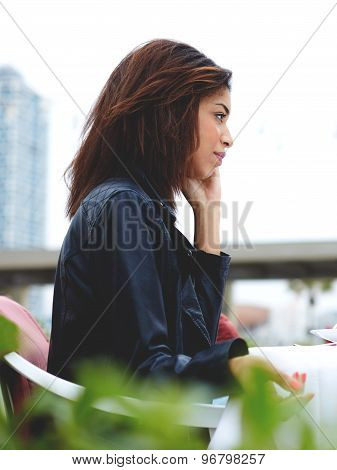 Pretty afro american woman talking on the smart phone while sitting at coffee shop terrace