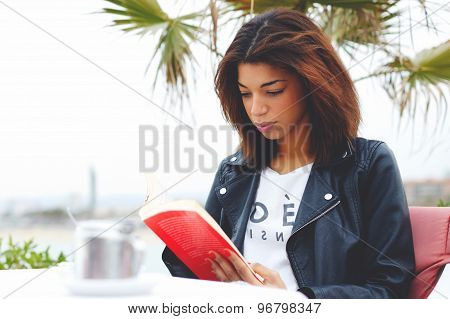 Afro american female enjoying a good book or novel during her recreation time outdoors at weekend