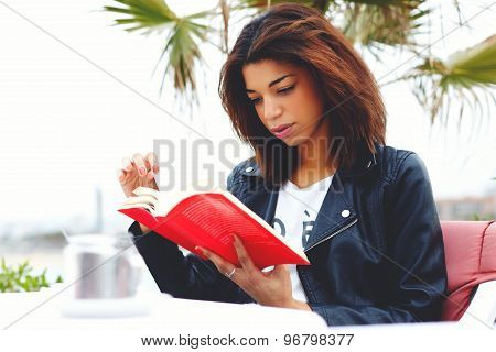 Attractive afro-american female reading fascinating book while sitting on the terrace of coffee shop