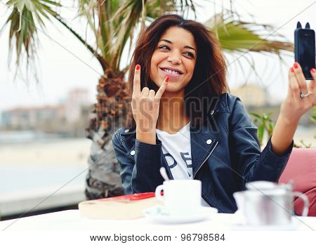 Afro american woman having fun while photographing herself with smart phone in coffee shop