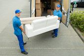Two Happy Male Workers Putting Furniture And Boxes In Truck poster