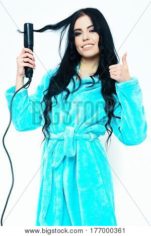 pretty cute smiling sexy girl or beautiful woman with fashion makeup do hairstyle and posing in turquoise velour bathrobe with straightener isolated on white background
