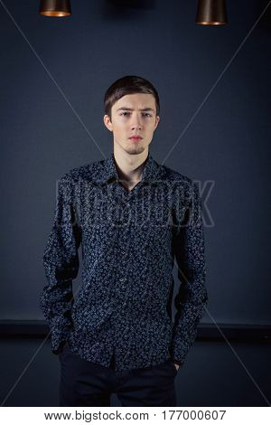 Serious handsome young man with beard wearing dark shirt standing holding hands in pockets