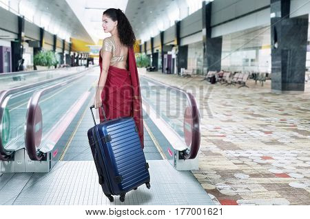 Back view of Indian woman wearing saree clothes and walking on the escalator while carrying bag shot at airport