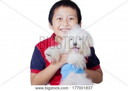Image of little boy hugging Maltese dog while standing on the studio isolated on white background