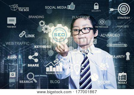 Portrait of a little businessman pressing a virtual SEO button on the futuristic screen. SEO concept