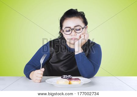 Image of overweight woman feeling bored with donuts on a plate while holding fork