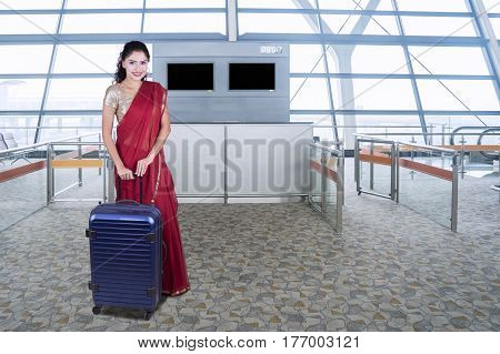 Beautiful Indian woman standing in the airport terminal while holding a suitcase and wearing a red saree clothes