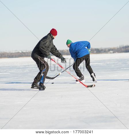 Dnepr Ukraine - January 22 2017: Two mature man fighting for the pack while playing hockey on a frozen river Dnepr in Ukraine