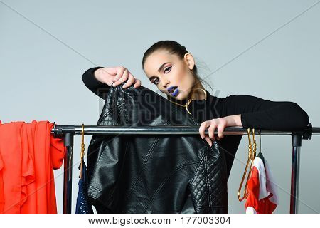 Pretty girl or sexy woman slim fashion model with sexi blue lips in bodysuit posing with clothing and black leather jacket on hangers at clothes rack wardrobe on grey background