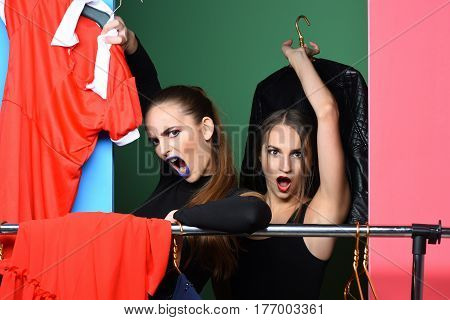 Two Angry Pretty Girls Shouting At Clothes Rack