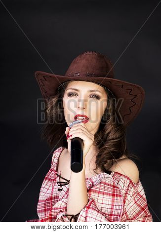 Beautiful brunette cowgirl in cowboy hat  singing on black background
