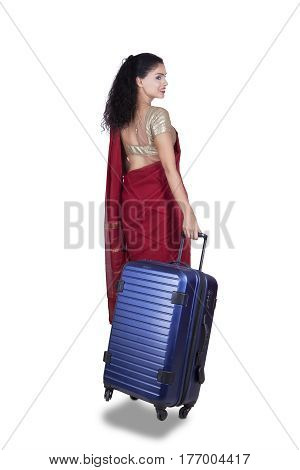 Rear view of Indian woman walking in the studio while wearing a red saree and carrying a suitcase