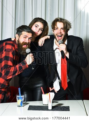 Happy friends celebrating at karaoke party on white curtain. Smiling pretty girl or beautiful woman and two bearded men hipsters with beards in red plaid shirt and business suit singing
