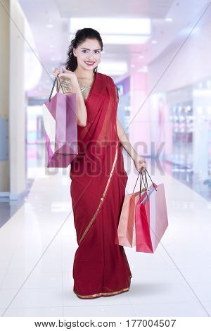 Beautiful young woman standing at the mall while wearing a red saree clothes and holding shopping bags